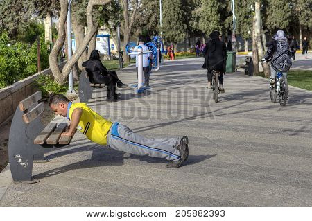 Fars Province Shiraz Iran - 19 april 2017: Routine morning workout in the city park of rest mature man doing push-ups using a park bench.
