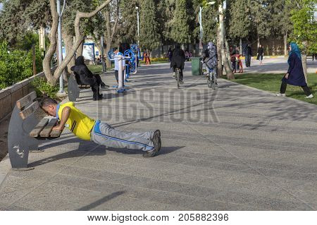 Fars Province Shiraz Iran - 19 april 2017: Routine morning training in a city recreation park a mature man doing exercises using a park bench.