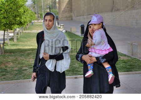 Fars Province Shiraz Iran - 19 april 2017: A Muslim family a young woman a mature woman and a little girl are walking along city streets near the Karim Khan castle.