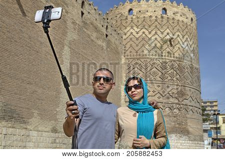 Fars Province Shiraz Iran - 19 april 2017: A young Iranian couple takes a picture of themselves against the walls of an ancient castle using a self-stick and a smartphone.