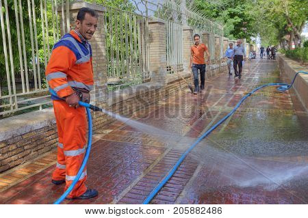Fars Province Shiraz Iran - 19 april 2017: Street worker washes the pavement using a hose connected to the urban water supply.