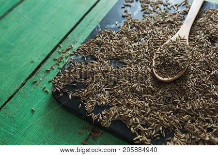 Close-up of cumin with spoon in tray on wooden table