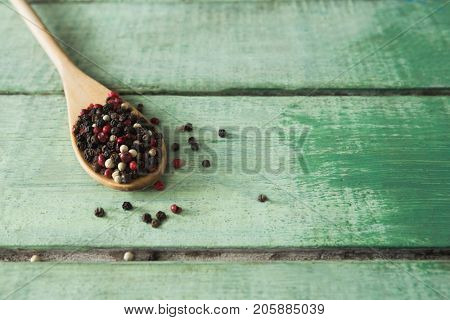 Mix peppercorns in spoon on wooden table