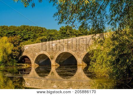 Large brick bridge with arched tunnels spanning a river with its reflection in the water surrounded by lush green trees with a clear blue sky.