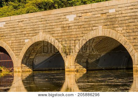 Closeup of large brick bridge with arched tunnels spanning a river