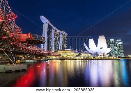 SINGAPORE- September 6 2017: The brightly lit Helix Bridge leads to the Marina Bay Sands hotel with the iconic ArtScience Museum in the background.