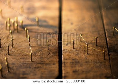 Connected. Overcoming divides and obstacles and linking separated people and groups. Networking, social media, internet communication abstract concept image. Web of gold wires on rustic wood.