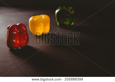 Colorful carved bell peppers on table during Halloween