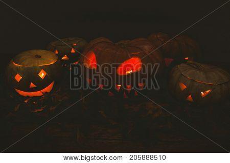 Illuminated jack o lanterns in darkroom during Halloween