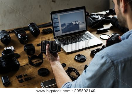 A man holding a camera lens and preview photo on laptop