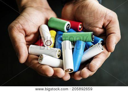 Closeup of hands holding various alkaline battery