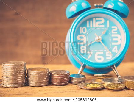Retro stack of coins and alarm clock on wooden background. Business Finance and time of money concept.