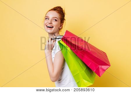 Side view of happy ginger woman holding packets on shoulder and looking back over yellow background