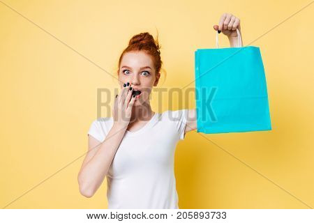 Surprised ginger woman holding packet in hand and covering her mouth over yellow background