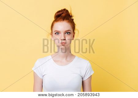 Pretty ginger woman in t-shirt with puffed cheeks looking at the camera over yellow background