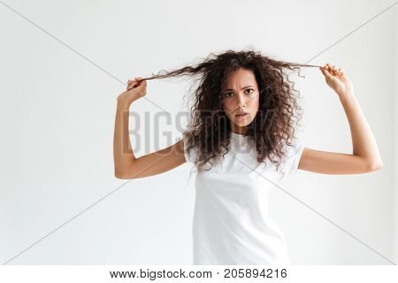 Frowning unsatisfied girl touching her hair and looking at camera isolated over white background