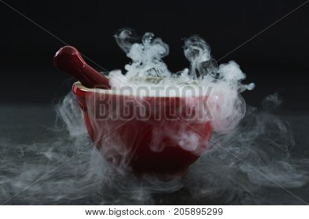 Close-up of dry ice smoke in bowl on black background