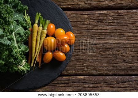 Overhead of mustard greens, carrots and tomatoes on tray