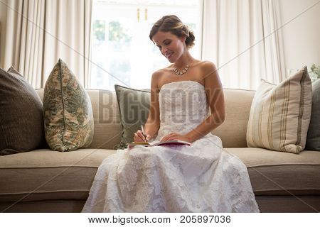 Low angle view of beautiful bride writing in diary while sitting on sofa at home