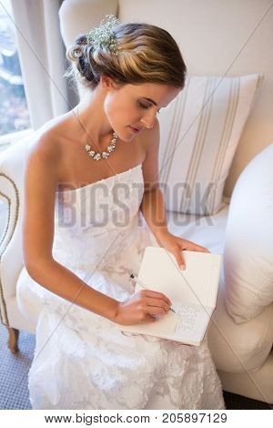 Beautiful bride writing in diary while sitting on armchair at home