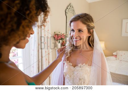 Beautician dressing up beautiful bride at home
