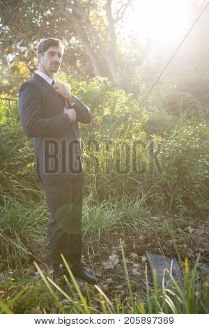 Portrait of confident bridegroom adjusting necktie while standing in park