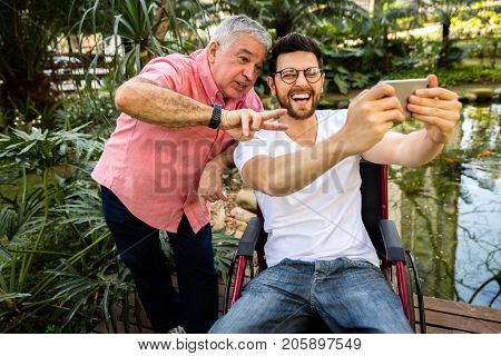 Dad and son sitting in his wheelchair taking selfie and having fun in the park