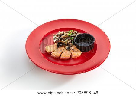 Teppanyaki Japanese and Korean Grill Food - Salmon with vegetables mushrooms on sauce on red plate on a white isolated background. Pan Asian menu