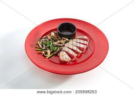 Teppanyaki Japanese and Korean Grill Food - tuna with vegetables mushrooms with sauce on red plate on  white isolated background. Asian menu