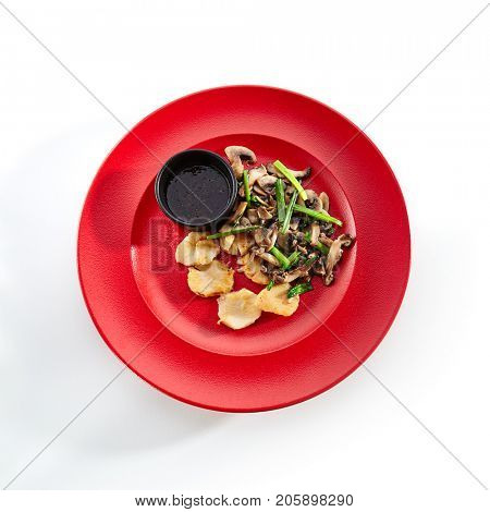 Teppanyaki Japanese and Korean Grill Food - Sea scallop with vegetables mushrooms on sauce on  red plate on white isolated background. Pan Asian menu. Top View
