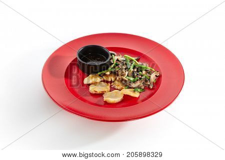 Teppanyaki Japanese and Korean Grill Food - Sea scallop with vegetables mushrooms on sauce on  red plate on white isolated background. Pan Asian menu