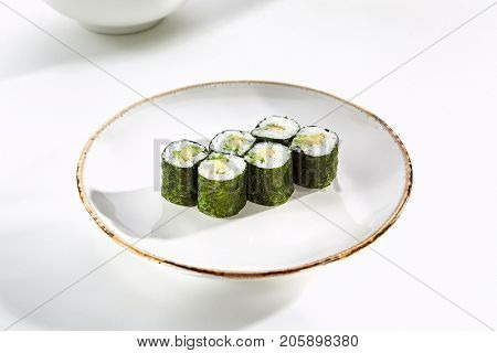 Classic maki rolls with avocado served on white flat plate. Asian menu for gourmets in luxury restaurant