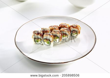 Kanada sushi rolls with salmon, eel, Philadelphia cheese, avocado and cucumber served on white flat plate. Asian menu for gourmets in luxury restaurant