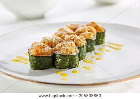 Maki rolls topped with fish served on white flat plate. Asian menu for gourmets in luxury restaurant
