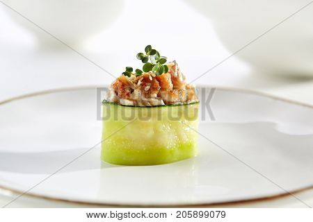 Sushi in cucumber with smoked eel with fresh herbs on  white plate with  gold border. Asian restaurant menu