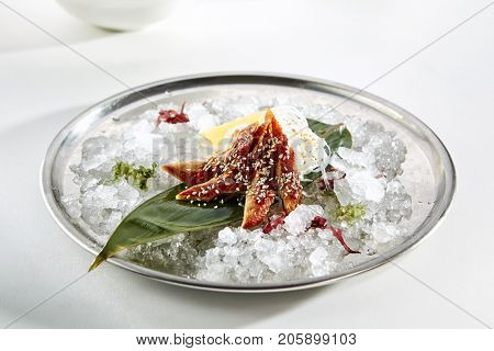Sashimi with eel with  slice of lemon fresh greens on bamboo leaf and in plate full of ice