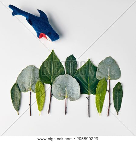 Nature Minimal Concept - Forest Treeline made of green leaves with shark toys on white background. Flat Lay