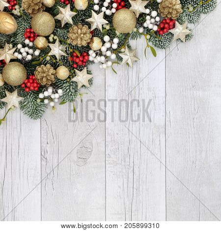 Christmas decorative background border with gold and white bauble decorations, holly, mistletoe and fir on rustic white wood background.