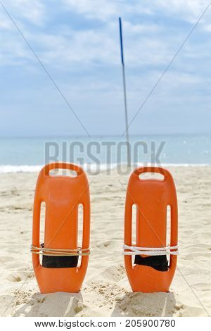closeup of some colorful rescue buoys in the sand of a quiet beach in the Mediterranean sea