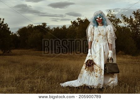 a scary evil clown wearing a dirty and ragged bride dress, and holding a bridal bouquet with wilt flowers and an old purse, in a disturbing rural landscape at dusk