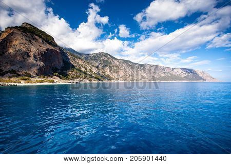Panoramic view of Crete (Greece) mountains of Libyan Sea side. driving with a boat along from Samaria gorge towards Loutro village. In background village Agia Roumeli.