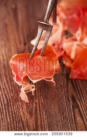 spanish jamon Cured Meat on large vintage meat fork  and wooden background