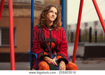 Young hipster woman sitting on the swing in city street. Stylish female fashion model in sweatshirt outdoor