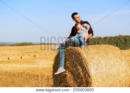 Happy father and 2 year old girl sitting on hay bales in harvested field