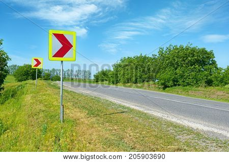 Warning signs for dangerous turn on country road.