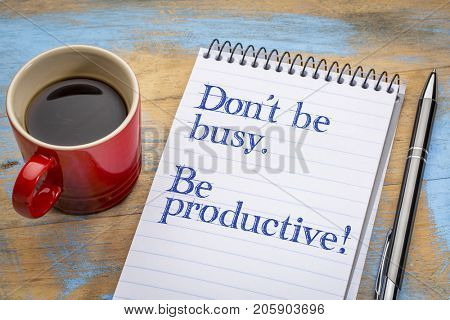 Don't be busy. Be productive. Handwriting in a spiral notebook with a cup of coffee.