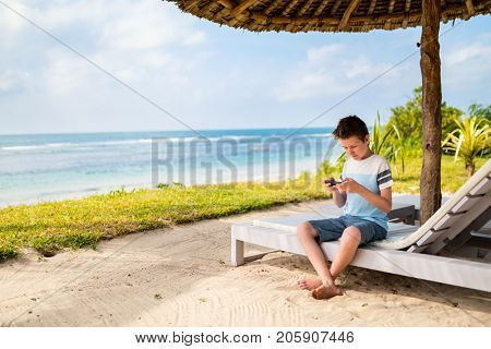Handsome pre-teen age boy playing on phone at tropical beach on summer vacation