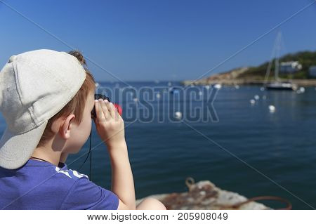 boy at the seaside looks through binoculars. child on the pier watches the boats in the sea. Copy space for your text