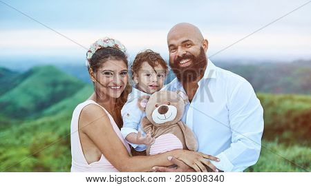 Smiling young latino family on natural blurred background