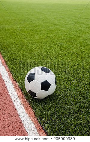 The football is on the artificial grass soccer field in the stadium.